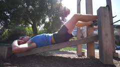 A man doing sit-ups at a park. Stock Footage
