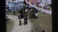 1962: mother carrying baby on her back and walking and a kid follows CALCUTTA Stock Footage