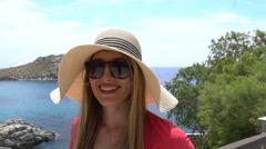 Blonde model walking large hat ocean background greek island slow motion Stock Footage