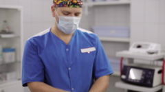 Doctor putting on medical glove in operating room Stock Footage