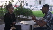 African American couple at a table in the city talking together Stock Footage