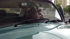 Beautiful woman in hat gets into rainy car Stock Footage
