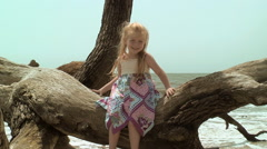 Red head toddler girl sits on dead tree on beach Stock Footage