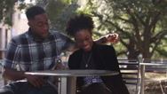 African American couple at a table in the city smiling for the camera Stock Footage