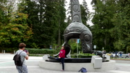 People taking picture beside Vancouver aquarium totem Stock Footage