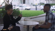 Couple at a table taking pictures with a phone, then looking at them together Stock Footage