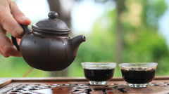 The tea ceremony in the garden. Puer tea is poured into cups. Close-up. Stock Footage