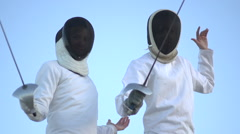 A man and woman fencing on the beach. Stock Footage