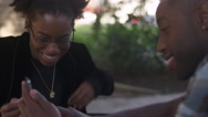 African American couple looking at pictures on a cell phone Stock Footage