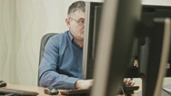 Stuff in Office: man in glasses in front of desktop computer, dolly shot Stock Footage
