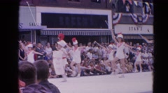 1964: marching pageantry through the street witnessed by many people  HARVARD Stock Footage