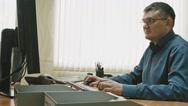 Office worker in glasses in front of desktop computer, slide shot Stock Footage