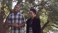 African American couple smiling in front of a tree Stock Footage