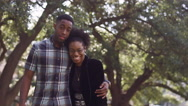 African American couple smiling and embracing in front of a tree Stock Footage