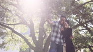 African American couple taking a picture together in front of a tree Stock Footage