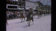 1964: people in various costumes riding horses through the street in a parade  Stock Footage