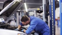 Mechanic man with lamp repairing car at workshop 43 Stock Footage