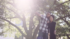 African American couple taking funny pictures together in front of a tree Stock Footage