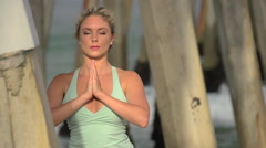 A young attractive woman doing yoga on the beach under a pier. Stock Footage