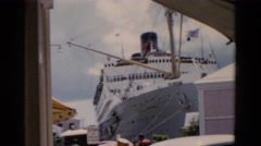 1951: people walk around vehicles parked and moving in front of docked cruise Stock Footage