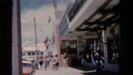 1951: pedestrians stroll down sidewalk on commercial block of storefronts. Stock Footage