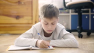 A Boy lying on the floor in her room doing homework. Horizontal shot Stock Footage