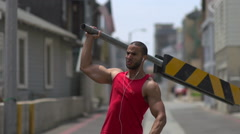 A man working out in an urban alley, doing shoulder press with a road barricade Stock Footage