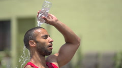 A man pouring water over his head and resting after a intense workout. Stock Footage