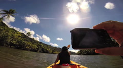 POV of a man taking a picture of a woman kayaking at Raiatea Island on the Faaro Stock Footage