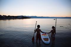 Silhouette of beautiful couple with sup surf and paddle at the ocean. Concept Stock Photos
