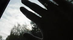 Close-up of hand with rings on the window of car on the go. Sun shining through Stock Footage