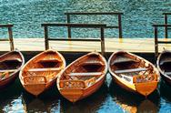 Small wooden boats docked and tied to empty pier Stock Photos