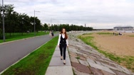 Thoughtful young woman go on shore front promenade, slow motion Stock Footage