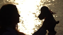 Girl hold toy against face, hug it, silhouette portrait, shining sea water Stock Footage