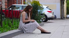 Brunette woman sit on border stone in city downtown talk cell phone Stock Footage