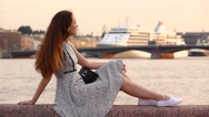 Thoughtful brunette woman sit on parapet against cruise ship, slow motion Stock Footage