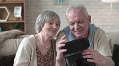 Curious Elderly Couple Looking at VR Goggles Stock Footage
