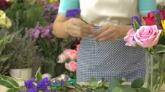 Dolly shot of florist woman cutting and arranging flowers in a glass vase Stock Footage
