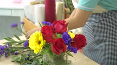 Florist woman cutting flowers and arranging beautiful flowers in a glass vase Stock Footage