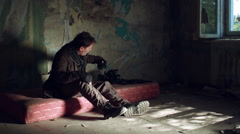 A man in a post apocalyptic clothes and a black gas mask comes in an abandoned Stock Footage