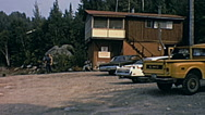 Canada 1970: cars parked outside a house in the forest Stock Footage