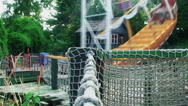 In the foreground a network woven from a large rope swing which sways from side Stock Footage