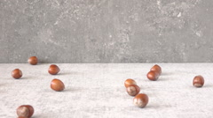 Hazelnuts falling in slow motion on stone table. Food film clip. Stock Footage