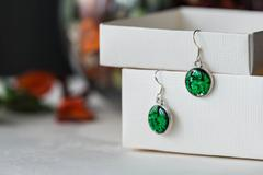 Handmade earrings made of epoxy resin and glitter closeup Stock Photos