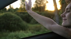Pretty woman traveling by car in summer. Hand playing with wind through the Stock Footage