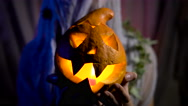 Halloween Witch with a magic Pumpkin in a dark room. Beautiful young woman in Stock Footage