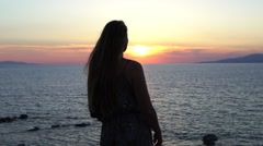 Blonde model raises her hands in the air ocean sunset silhouette mykonos greece Stock Footage