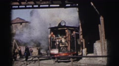 1962: a train with several people driving through a small town train station Stock Footage