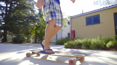 Person riding long board with sun shining from background 4K Stock Footage
