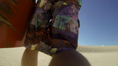 A young man sand boarding down a dune in the desert. Stock Footage